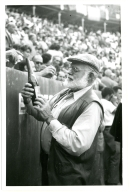 Hemingway at Bullfight Inspecting Wine Bottle