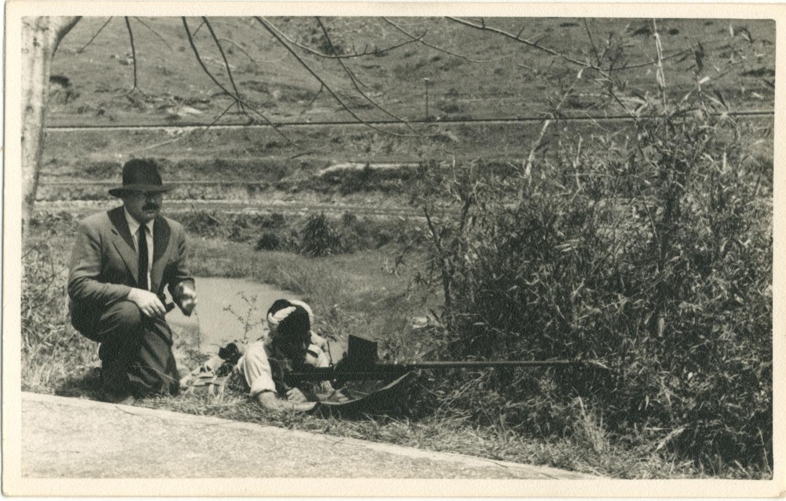 Hemingway in Suit Next to Prostrate Man Shooting a Gun