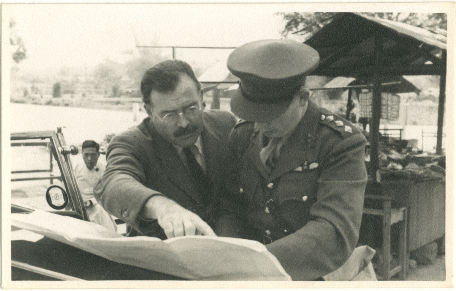 Hemingway Pointing to Document Held by Man in Army Uniform